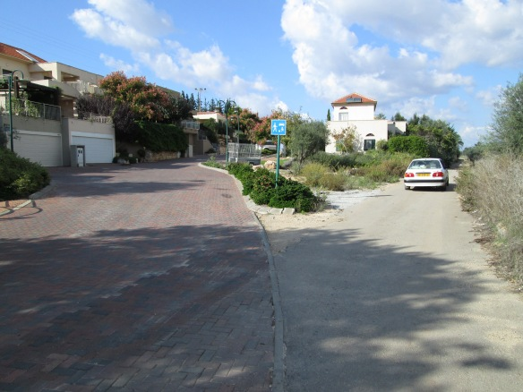 Left: a brick-paved road and an affluent Jewish community.  Right: A dirt path leading to a Bedouin village.